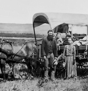 A pioneer family next to their covered wagon